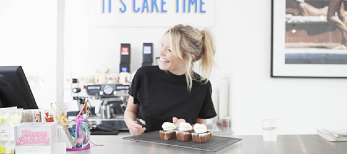 Blonde girl laughing in a bakery